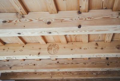 Rustikale Decke mit Innungslogo Schnitzerei von Hattinger Holzbau GmbH Pramet